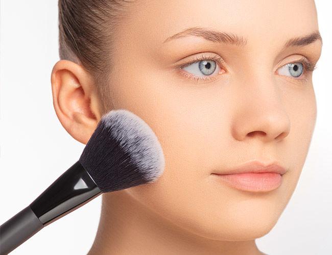 Mit Hilfe eines Make-up Pinsels wird Fixierungspuder aufgetragen