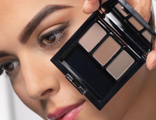 Augenbrauen Puder in der Beauty Box wird vor ein Gesicht gehalten