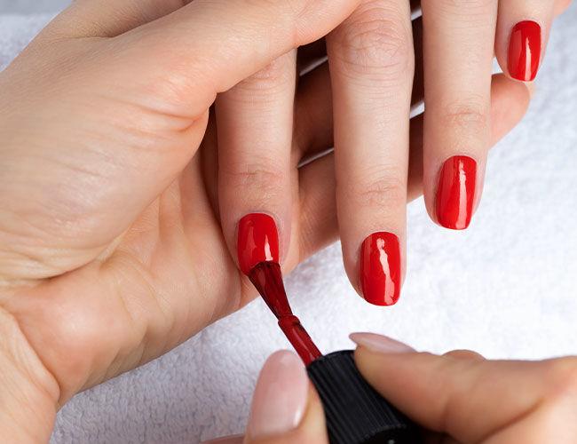 Du vernis à ongles rouge est appliqué