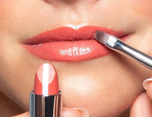 Ein pflegender Lippenstift wird mit einem Lippen-Pinsels aufgetragen