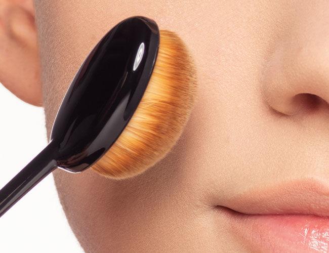 Un pinceau de maquillage est tenu sur une joue.