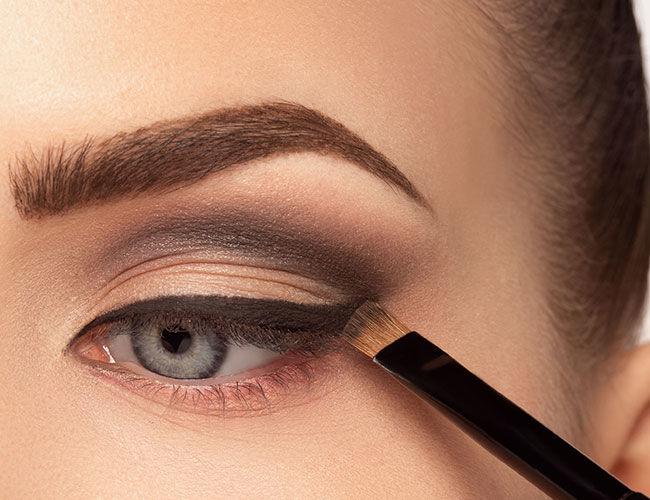 L'eyeliner est intensifié avec un fard à paupières noir et ombré avec un pinceau.