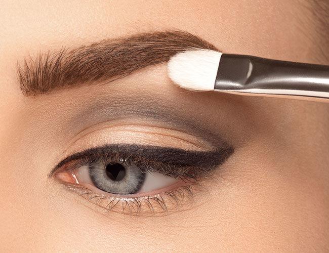 Une ombre à paupières légère est appliquée sous les sourcils.