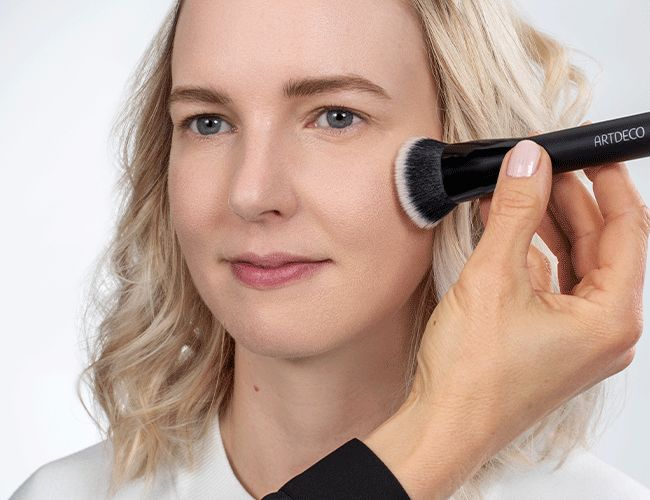 Das Make-up wird mit einem Fixing Puder mittels eines Pinsels eingeblendet