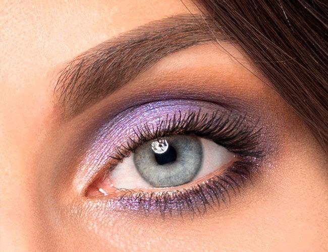 Es wird ein geschminktes Auge mit violettem Lidschatten gezeigt