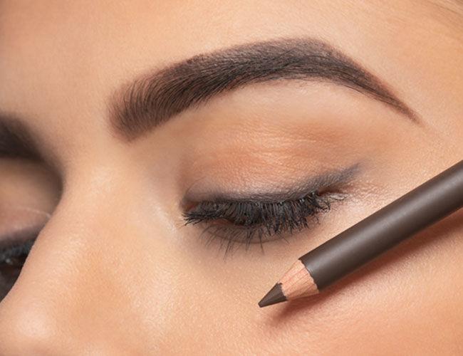 : Ein Augenbrauen Stift wird vor ein Gesicht gehalten