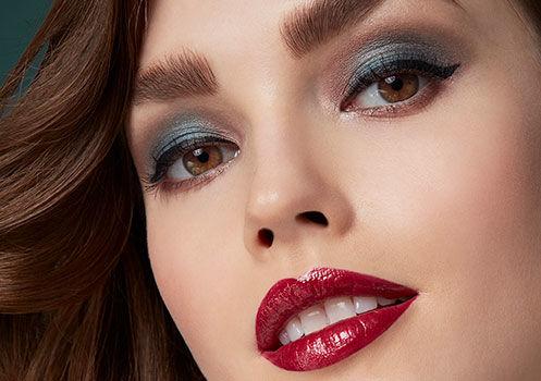 Ein Model mit einem starken Augen-Make-up und rot geschminkten Lippen
